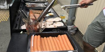 A man cooking hot dogs on a grill